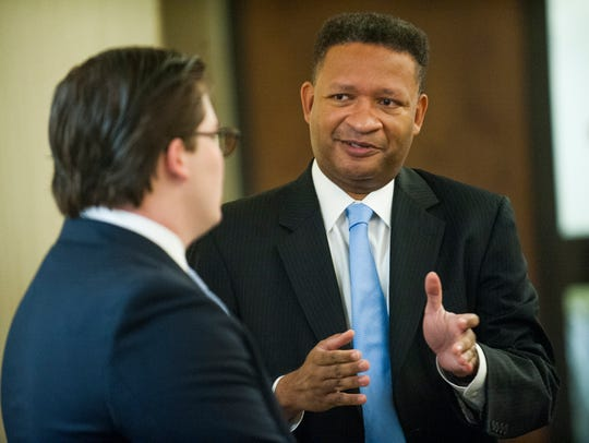 Artur Davis chats while waiting for his hearing at