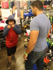 Damien Hernandez, 7, tries on a hooded sweatshirt he liked so much he wore it out of the store as his volunteer escort, Ray Felix, helps him shop at the 69th annual Children's Shopping Tour Saturday at Northridge Mall.