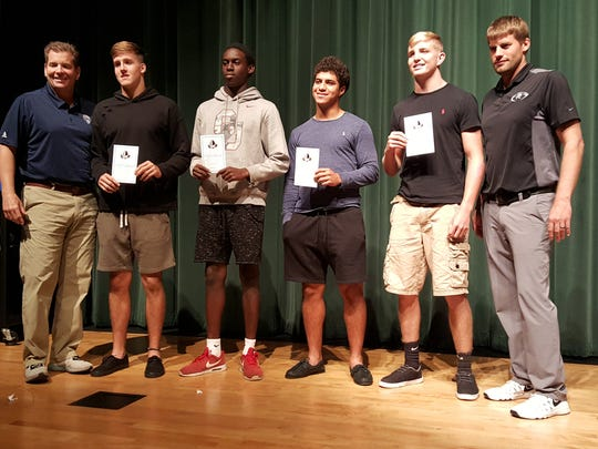 Palmetto Ridge football players display their invites to the U.S. Army National Combine, which includes the top 600 underclassmen in the country. The players were recognized during a ceremony at the school on Oct. 25, 2017. From left to right: Steve Quinn, vice president of All-American Games;  Max Hussain, junior linebacker; Voshon Siriac, sophomore safety; Cristian Torres, junior running back; Colby Singetary, sophomore linebacker; Chris Toukonen, Palmetto Ridge coach.