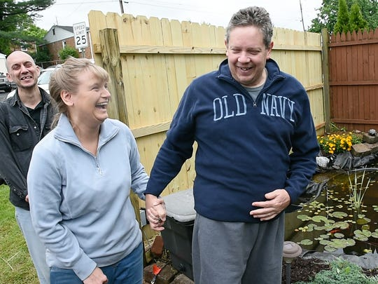 Denise Holtzinger and Tim Sprenkle, far left, surprised Charlie Holtzinger with a back yard oasis on Sunday. Charlie was released from the hospital following surgery and his wife and friends renovated his back yard to give him a place to recuperate.
