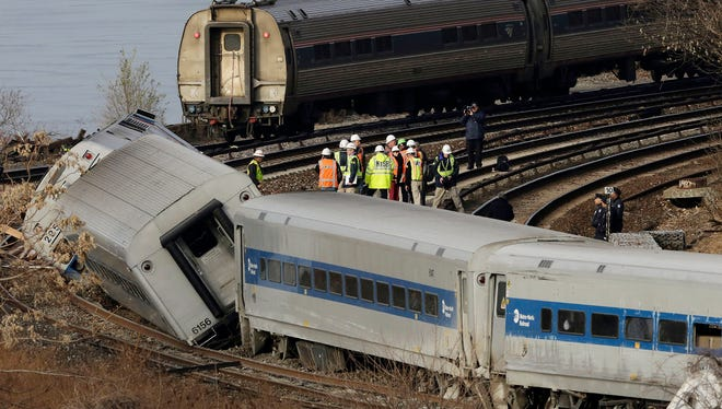 An Amtrak train, top, traveling on an unaffected track, passes a derailed Metro-North commuter train, Sunday, Dec. 1, 2013 in the Bronx borough of New York. The Metro-North train derailed on a curved section of track early Sunday, coming to rest just inches from the water, killing at least four people and injuring more than 60, authorities said. Police divers searched the waters to make sure no passenger had been thrown in, as other emergency crews scoured the surrounding woods.  (AP Photo/Mark Lennihan) ORG XMIT: NYML111