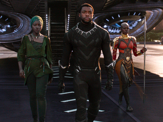 Chadwick Boseman in a screenshot as the superhero Black Panther, walking out of a spacecraft with women on each side of him.