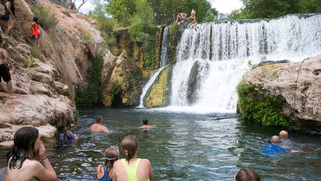 Swimmers watch as a couple jump off the old APS dam at Fossil Springs.