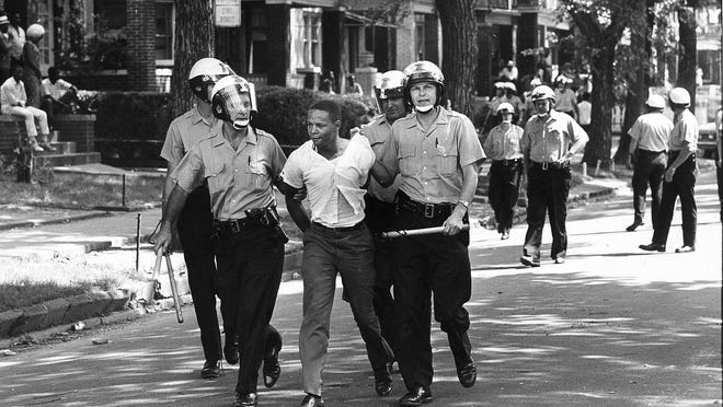 White police officers arrest a black man on 12th Street in Detroit on July 23, 1967.