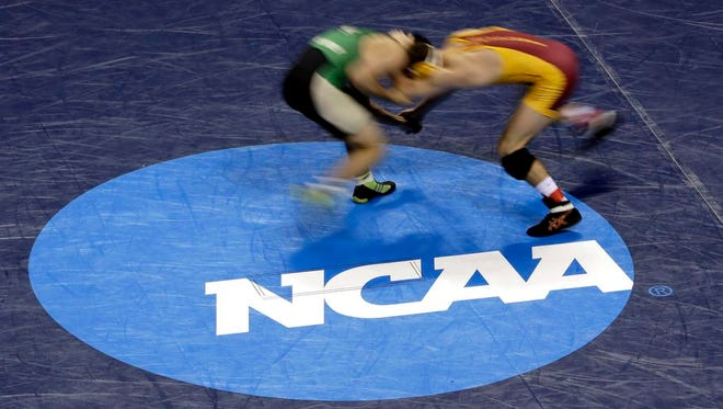 In this image taken with a slow shutter speed, Cal Poly's Dominic Kastl, left, and Iowa State's Tanner Weatherman wrestle during their 174-pound first-round match Thursday, March 19, 2015, at the NCAA Division I Wrestling Championships in St. Louis. (AP Photo/Jeff Roberson)