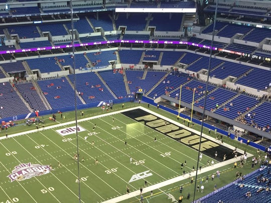 Purdue players warming up on the field at Lucas Oil