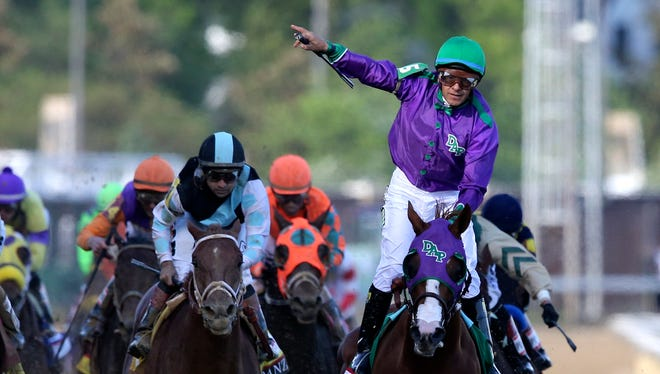 Victor Espinoza celebrates aboard California Chrome as they win the Kentucky Derby. May 3, 2014.