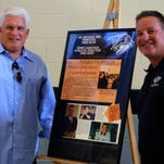 Dr. Michael Bee (center) and Terry Sawchuk (right) watch Plymouth athletic director Kyle Meteyer hoist their Hall of Fame plaque during Monday's induction ceremony. Bee and Sawchuk were the high school's first principal and athletic director, respectively.