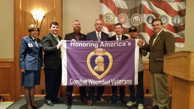 Rutgers-Camden student recipients of the Purple Heart for combat wounds hold the Purple Heart flag recently awarded the university by the Military Order of the Purple Heart. Air Force Lt. Gen. Gina Grosso is at left