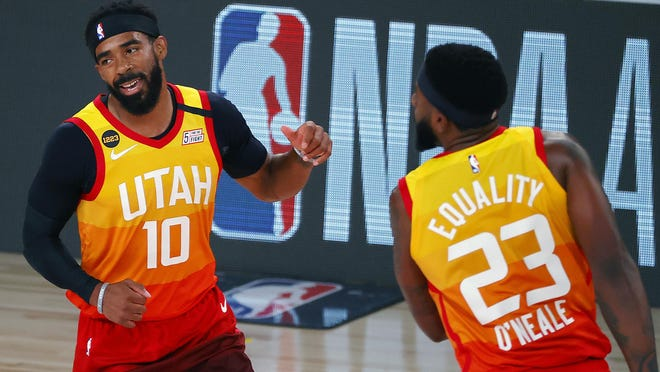Mike Conley (10) of the Utah Jazz celebrates a three-point basket with teammate Royce O'Neale (23) during the first quarter of a game against the Denver Nuggets at The Arena at ESPN Wide World Of Sports Complex on August 08, 2020 in Lake Buena Vista, Florida.