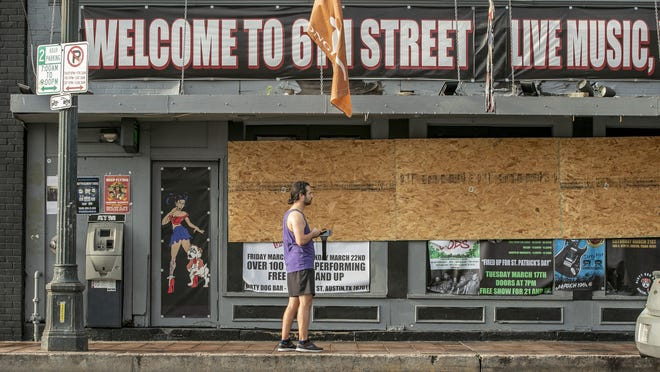 Douglas Allen Adden panhandles on South Lamar Boulevard near Barton Springs Saloon on Wednesday. The bar has reopened as a restaurant during restrictions on bars during the coronavirus pandemic.