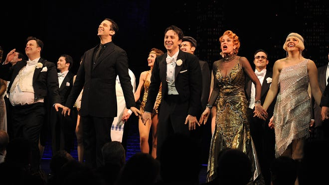 """Actor Nick Cordero, left, Zach Braff, Marin Mazzie and Betsy Wolfe on stage during the curtain call for the opening night of """"Bullets Over Broadway"""" at the St James Theatre on Thursday, April 10, 2014, in New York. Cordero died Sunday at Cedars-Sinai hospital from complications of the coronavirus."""