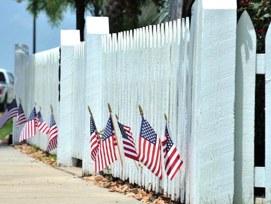 American flags line a fence in Sugar Mill Pond