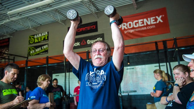 Athlete Randy Taylor lifts as judge Jon Light, left, looks on at the Adams County Special Olympics Powerlifting Meet at CrossFit Hanover on June 26, 2016.