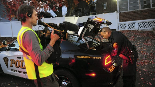 """In this Nov. 3, 2016 photo, a crew from the television program """"Live PD,"""" a reality show by the A&E Network, records an officer from the Bridgeport Police Department while on patrol in Bridgeport, Conn."""