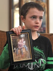 Kaleb Finley holds up a picture of himself and his grandmother, Linda Perry.