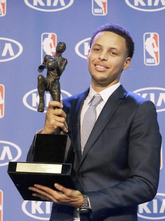 Golden State Warriors guard Stephen Curry holds the NBA's Most Valuable Player award at a news conference Monday in Oakland, Calif. Curry carried the top-seeded Warriors to a franchise-record 67 wins and surpassed his own record for most 3-pointers in a season.