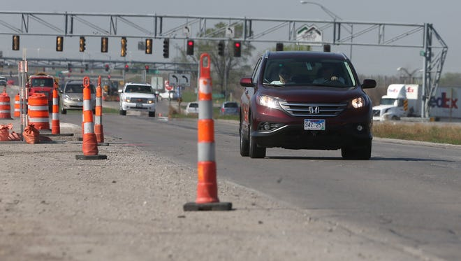 Traffic passes along the construction zone on Highway 65 in Altoona on Friday, April 17, 2015, as the construction project on Hwy 65 and Interstate 80 continues to make progress.