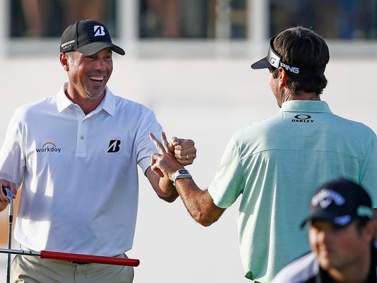 Matt Kuchar, left, smiles as he tries a fist bump with Bubba Watson, right, after Kuchar nearly holed out for an eagle, settling for a birdie, at the 17th hole during the first round of the Waste Management Phoenix Open golf tournament Thursday, Feb. 2, 2017, in Scottsdale, Ariz. (AP Photo/Ross D. Franklin)