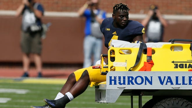 Michigan running back De'Veon Smith is carted off the field in the second half of a 31-0 win over Brigham Young on Saturday, Sept. 26, 2015, in Ann Arbor.