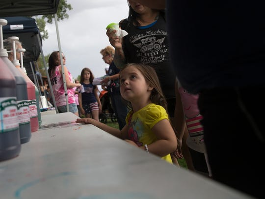 Jade Jones waits for her snow cone Tuesday during Aztec's National Night Out event at Minium Park.