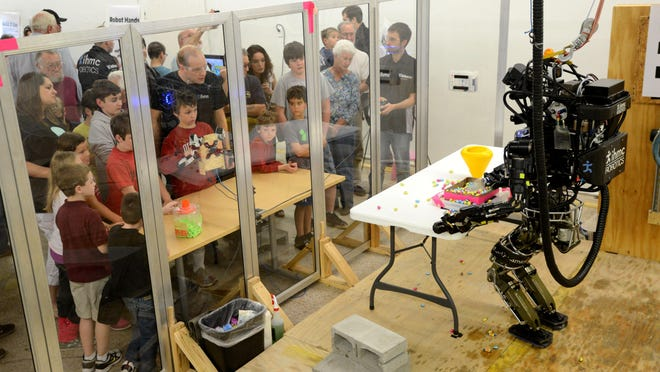 Atlas, a humanoid robot, is controlled by attendees of an April 2014 open house at IHMC. An open house will be held Thursday, Sept. 3, to celebrate the robotics team's second-place finish at this summer's DARPA Robotics Challenge in Pomona, Calif.