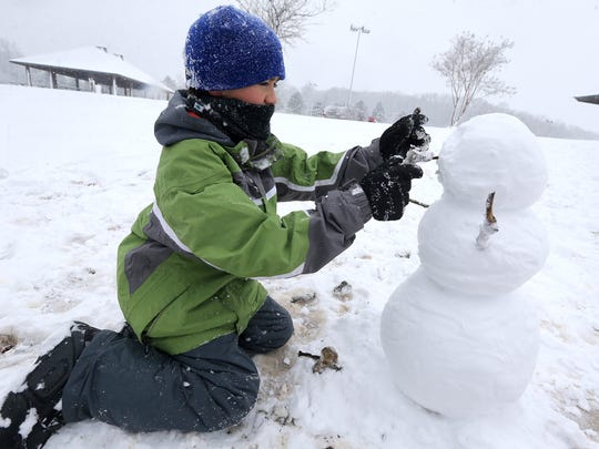 Jake Garland, 12, works to create a face for his snowman that he built at Barfield Crescent Park on Friday, Jan. 22, 2016, in Murfreesboro.