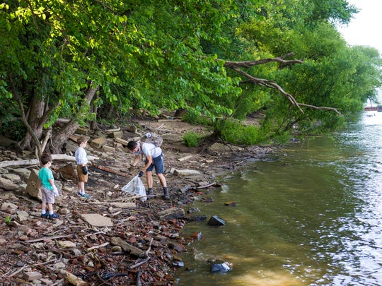 Mark Atwood, of Westwood, collects trash with his sons Norman, 5, and Charlie, 3, at the Ohio River sweep at Fernbank Park in Sayler Park Saturday, June 18, 2016.   The River sweep is Co-sponsored by the Ohio River Valley Water Sanitation Commission (ORSANCO).