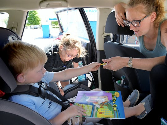 Oskar Buttiens, 3, hands his mother Sarah, of Shrewsbury Township, a crayon he received during the Safe Kids York County child seat safety check as Alice Price of WellSpan Health checks the fit of his car seat at the Kohl's parking lot in Springettsbury Township Thursday, July 12, 2018. The Safe Kids Buckle Up team included representatives from the Center for Traffic Safety, WellSpan Health, Springettsbury Township Police, York Area United Fire and Rescue and Pennsylvania State Police. Car seat safety checks in your area can be found by calling Safe Kids York County at 888-232-SAFE (7233). Bill Kalina photo