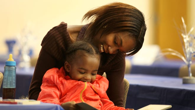 Desiray Thompson and her daughter Astoria Boone read a book before the Monroe County's Nurse-Family Partnership graduation. Thompson spent 30 months working one-on-one with a nurse from Visiting Nurse Service learning how to care for Astoria.