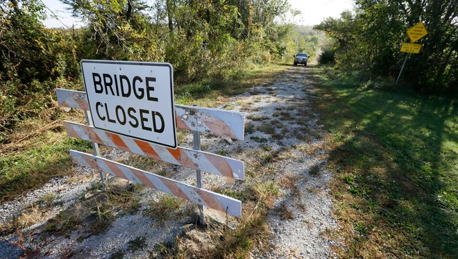 Duane Ohnemus drives his truck down a dirt road around a bridge closed sigh near his farm in Milo. The bridge closure has caused problems for Ohnemus and his wife, Mary Jo, raise cattle, corn and soybeans on 1,500 acres their family has owned for more than a century.