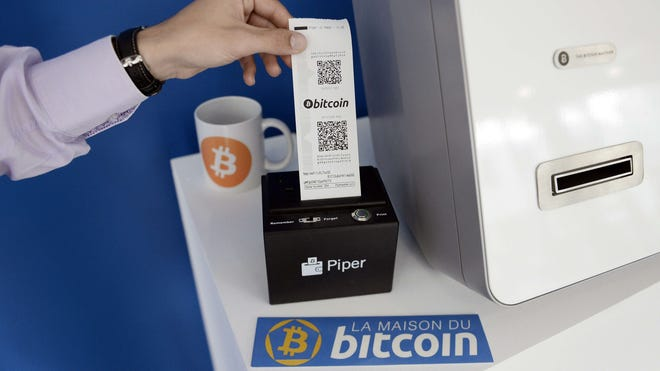 A man takes a receipt from a Bitcoin (virtual currency) dispenser at La Maison du Bitcoin in Paris in this June 2014 file photo.