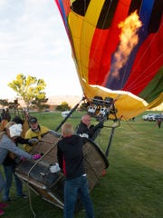 Mike Shrum's hot air balloon is prepared for takeoff at the Lake Powell National Golf Course in Page Sunday, Nov. 8, 2015. A weekend filled with fantastic ballooning weather saw 60 hot air balloons filling the skies over Lake Powell during the Page Lake Powell Hot Air Balloon Regatta on Friday, Saturday and Sunday mornings. In additions, about 20 of the balloons were lined up along Lake Powell Boulevard Saturday night for a balloon glow and street festival.