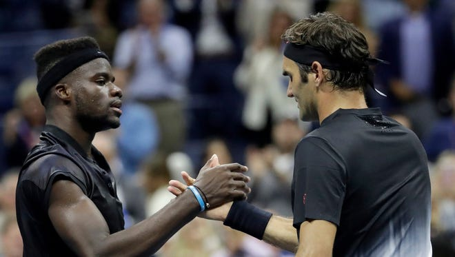 Roger Federer, right, of Switzerland, and Frances Tiafoe, of the United States, shake hands after Federer won their first round match at the U.S. Open tennis tournament, Tuesday, Aug. 29, 2017, in New York.