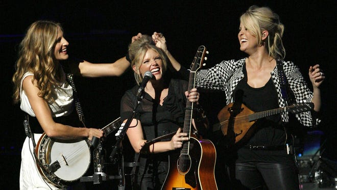 Emily Robison, left, and Martie Maguire, right, adjust Natalie Maines' hair as the Dixie Chicks perform in 2007 at the new Nokia Theatre in Los Angeles.