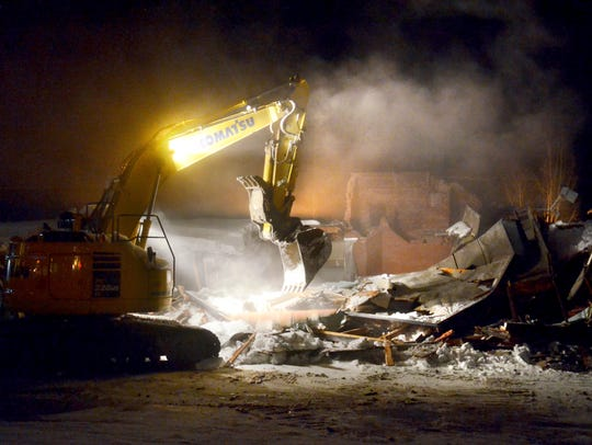 An excavator is used to demolish a commercial Frank