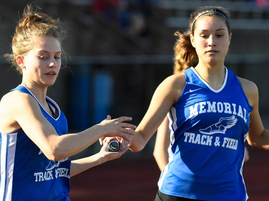 Memorial's Mallory Wittmer hands off to teammate Claire Vogel in the girls 3200 meter relay finals at the Evansville City Track meet held at Central High School Thursday, April 12, 2018.
