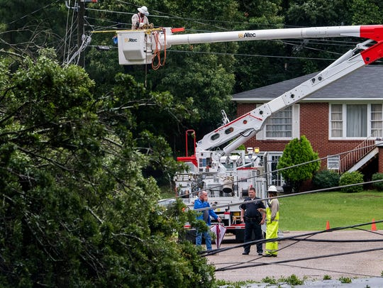 Workers work on downed power lines that are blocking