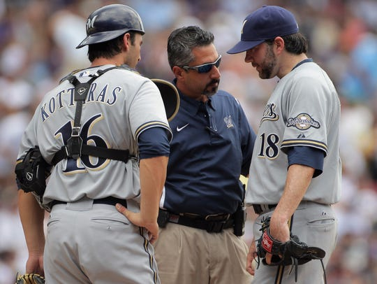 In his final season as the Brewers' head trainer, Roger Caplinger, now the team's medical director, consults with pitcher Shaun Marcum (right) and catcher George Kottaras during a game in 2011.