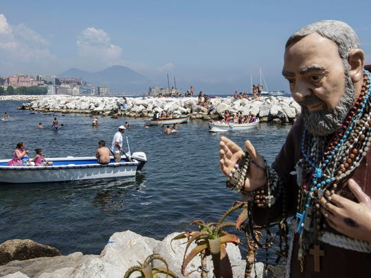 A statue of Padre Pio covered with rosaries stands nearby as people enjoy the sun and water at Mergellina Bay, in Naples, Italy. In the background is Mt. Vesuvius.