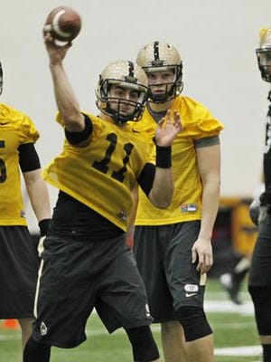 Freshman quarterback David Blough, 11, passes the ball as fellow quarterbacks Danny Etling, from left, Elijah Sindelar and Austin Appleby look on during the first day of spring football practice Tuesday, March 10, 2015, in the Mollenkopf Athletic Center on the campus of Purdue University.