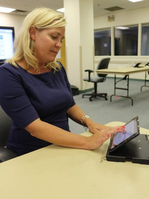 Hamilton County Board of Elections Executive Director Sherry Poland demonstrates one of the board's new e-poll books.