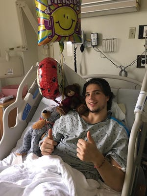 Kevin Fiala poses from his hospital bed following surgery to repair a fractured left femur.