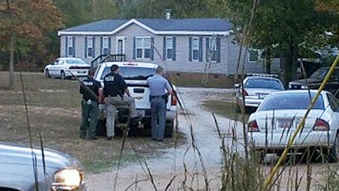 Law enforcement officials stand near a home where six people were found dead Oct. 29, 2013, in Greenwood, S.C.