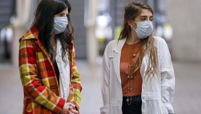 Women wear facial surgical masks in an effort to protect themselves from the influenza virus outbreak while waiting to change trains at a MARTA rail rapid transit system station in Atlanta, Georgia, on Feb. 8, 2018.