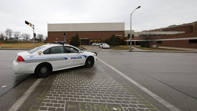 A city of West Allis police car drives past West Allis Central High School on March 9 when a bomb threat was called into the school earlier in the day, the third threat within a month.