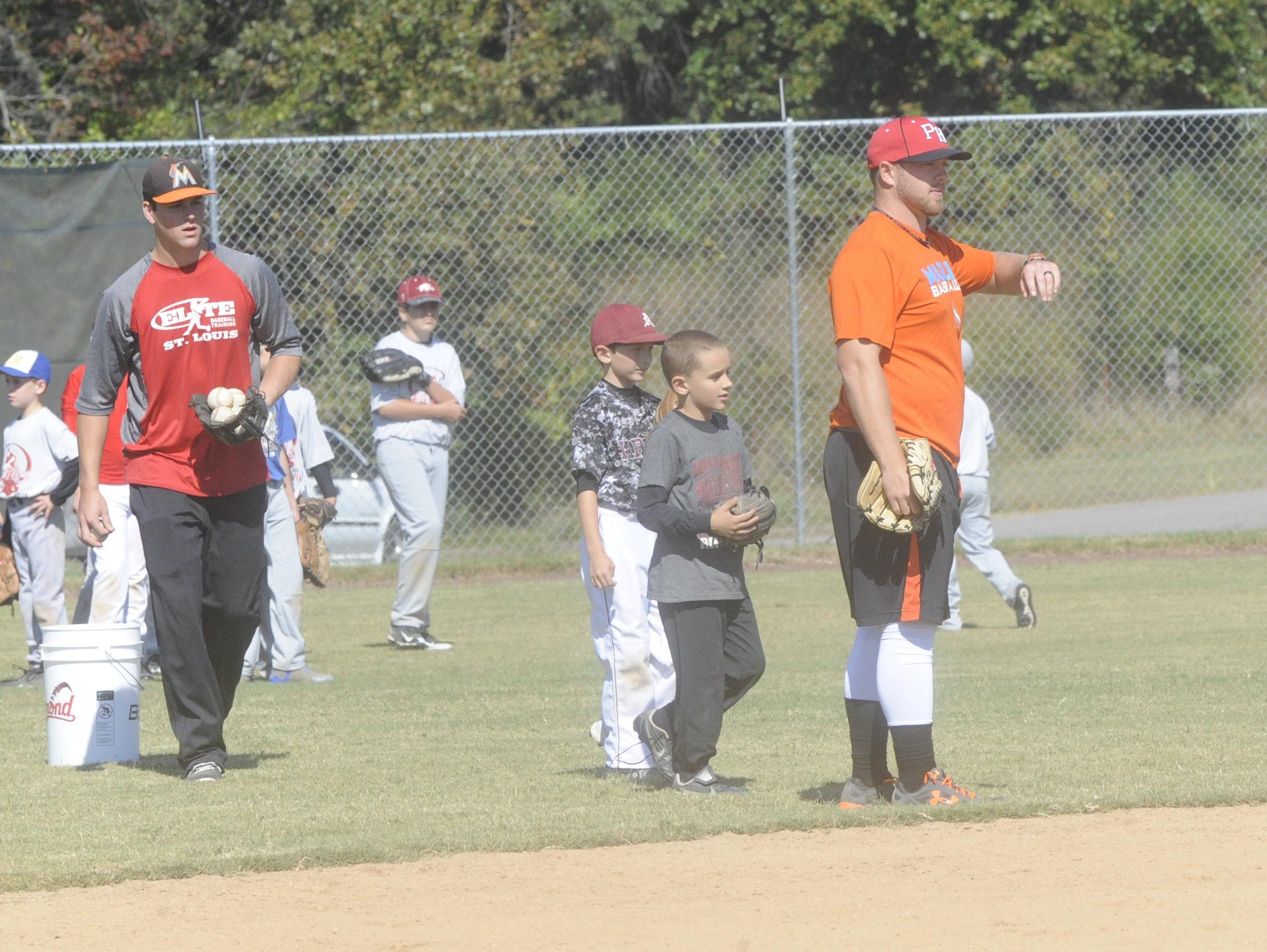 Former Arkansas Razorbacks Brian Anderson, left, and Colby Suggs, right, instruct players during the ProHogs Baseball Camp on Saturday at Clysta Willett Park.