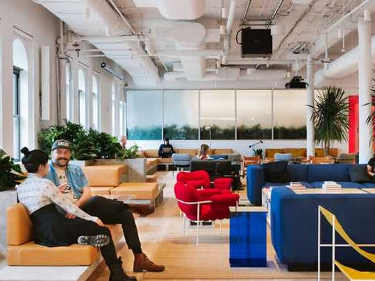 Two people sit inside the lobby of a trendy office.