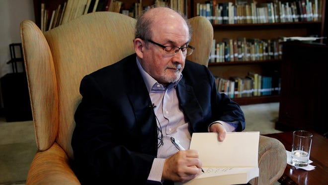 Indian-born British writer Salman Rushdie signs a copy of one of his books during an interview in Bogota, Colombia, Dec. 3, 2015.