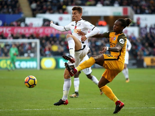 Swansea City's Tom Carroll, left, and Brighton & Hove Albion's Gaetan Bong battle for the ball during the English Premier League soccer match at the Liberty Stadium, Swansea, Wales, Saturday Nov. 4, 2017. (Nick Potts/PA via AP)